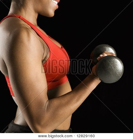 Torso of African American young adult woman lifting dumbbell.