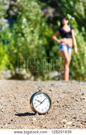 clock on the stone road and blurred brunette girl on a sunny day. time to travel concept