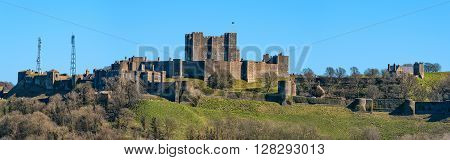 Dover United Kingdom - March 25 2016: Panoramic view to Dover Castle and St Mary church with copy space in sky. Castle was founded in the 11th century for protect the town and surrounding area for hundreds of years. Also known as Key to England.