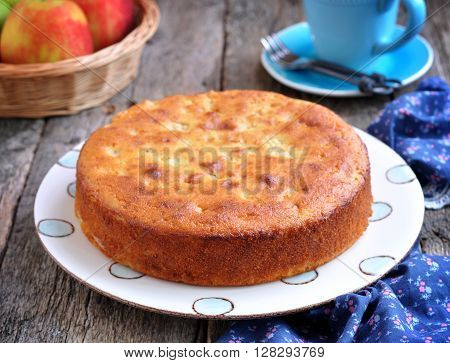 Sponge cake with cream cheese and apple on old wooden background.