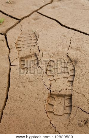 Boot Footprints In Dry Cracked Earth