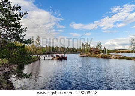 Wooden summerhouse on small island and sailing boats near small pier at river Daugava, Latvia