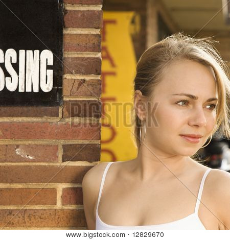 Attractive young Caucasian woman standing outside tattoo parlor.