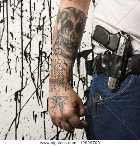 Caucasian tattooed man wearing holster with gun.