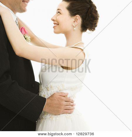 Caucasian groom and Asian bride dancing.