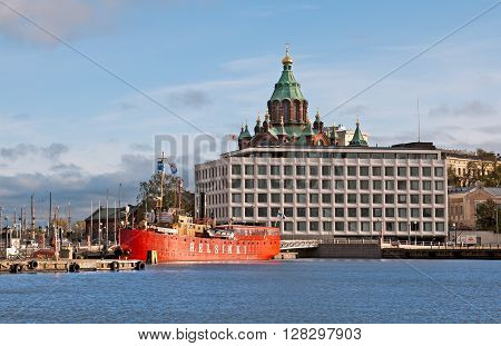 HELSINKI, FINLAND - OCTOBER 13, 2011: The main office of the Stora Enso Oyj Company, the Finnish pulp and paper manufacturer, On the background is Uspenski Cathedral. Foreground is red bar-ship