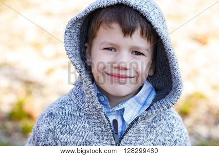 Little boy in hood smile outdoor at early spring or autumn