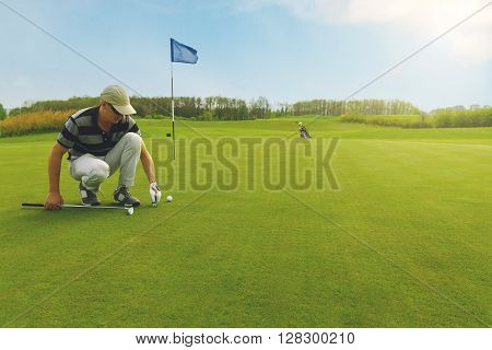 Male golfer marking ball position on the green