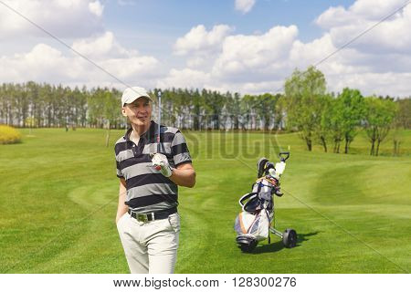 Portrait of male golfer standing at fairway on golf course