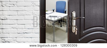 Welcome to the office. Half opened door to office. Door handle, door lock. Opening door. Privacy, safety concept. Entrance to the office workplace. Door at white brick wall, modern interior design.