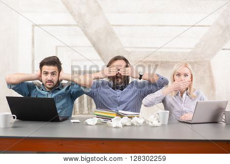 Frightened businessteam sitting at table and working. Business people closing their mouth, ears and eyes in office.