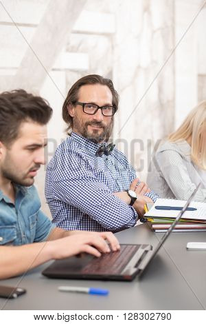 Picture of happy smiling businessman in glasses looking at camera. Businessteam coworking in office.
