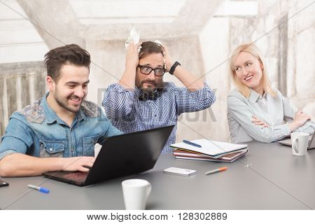 Coworking of businessteam in office upon business projects of their company. Happy people smiling while one of colleague looking stressed and frightened.