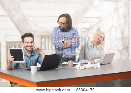 Businessteam working in office while their boss standing with his arms crossed. Happy people smiling and using computer devices: tablet PC, smart phone, laptop computer.