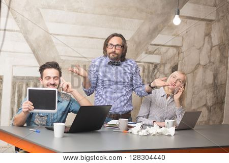 Picture of boss in glasses shrigging his shoulder while his happy workers working: using computer devices while talking over smart phones.