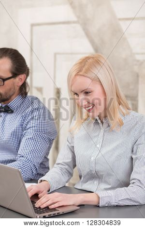 Business woman working on laptop computer and toothy smiling. Beatiful lady typing document: agreement or contract.