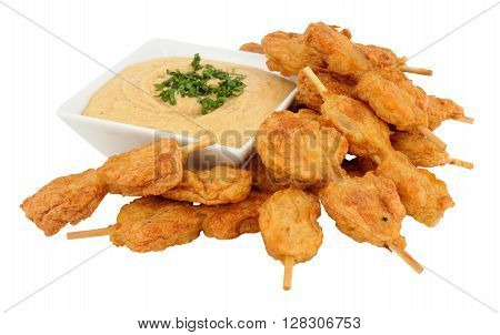Chicken satay skewers with dish of peanut dip isolated on a white background