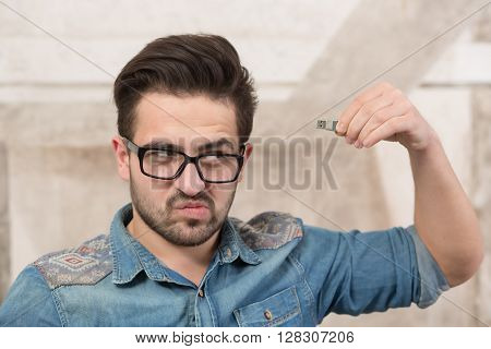 Freelancer in glasses holding usb card near his head and looking somewhere in office. Man having problems with memory.