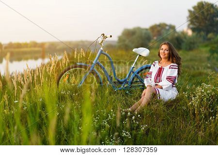 Woman in Folk costume with bicycle. Young attractive woman at the riverside having rest with bicycle in national ethnic ukrainian folk traditional costume or dress.