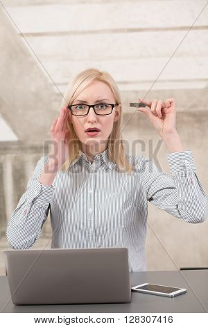 Freelance woman does not have enough memory for different data. Bautiful lady holding usb card near her memory in office.