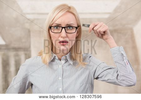 Sad freelance woman holding usb card in office. Beautiful lady in glasses looking at camera demonstrating about bad memory.