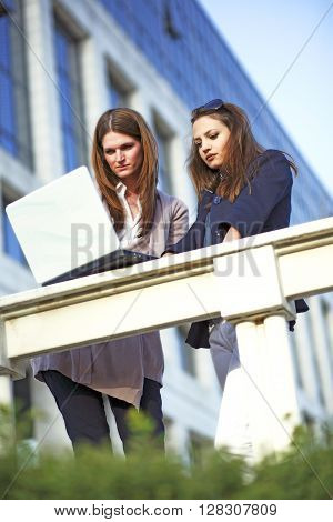 Two beautyful youg womans working together outside