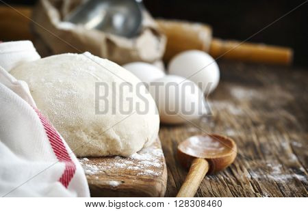 Fresh bread dough ready for baking on wooden table.
