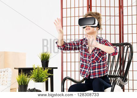 Happy woman getting experience using VR-headset glasses of virtual reality at home much gesticulating hands