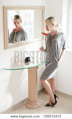 Fashion woman smelling gerbera flower near mirror