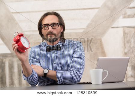 Handsome businessman holding alarmclock and looking away. Freelancer in glasses working in office on laptop computer.
