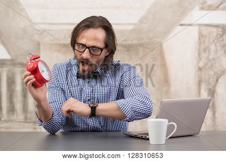 Businessman holding alarmclock and checking time with his watch on wrist. Handsome man in glasses looking shocked.