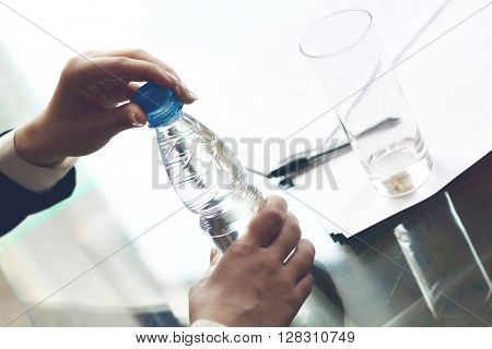 Business person opens a bottle of fresh water at desk