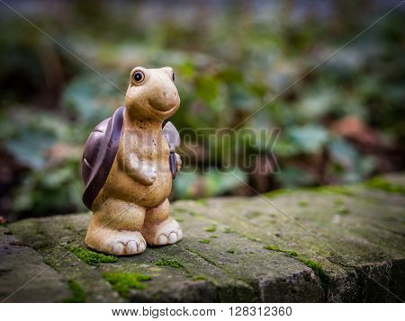 Small turtle figurine standing on a wall in the garden