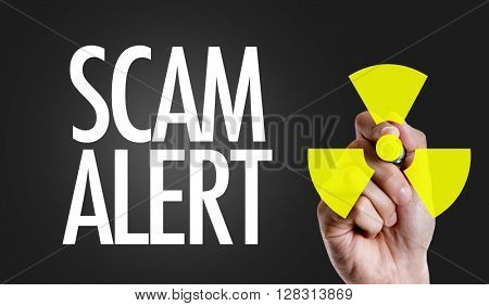 Hand writing the text: Scam Alert