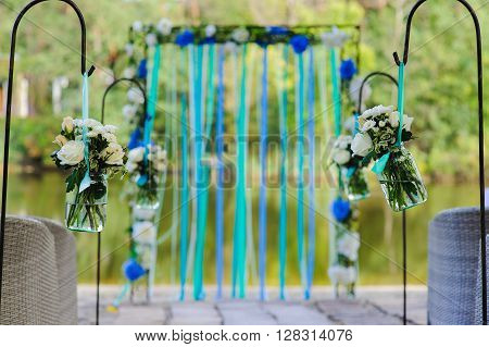 White roses and other flowers in two glass jar hung in wedding party. White roses, chrysanthemum in vase  with water. Wedding arch, decorated with colored ribbons on river bank. Wedding decorations.