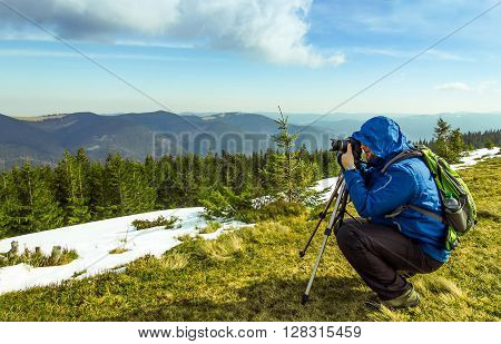 Lonely photographer in mountains taking the picture of a lonely pine tree