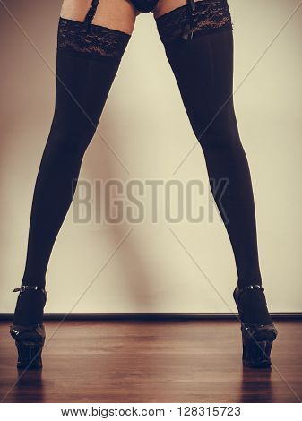 Sexuality of women. Part body woman wearing black sexy stockings. Long female legs in high heels.