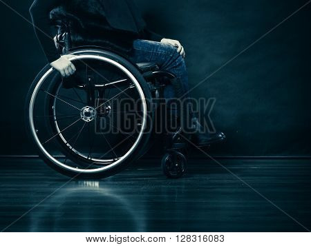 Real people disability and handicap concept. Young woman invalid girl sitting on wheelchair part of body studio shot on black