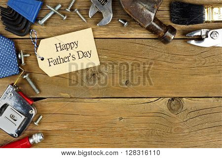 Happy Father's Day tag and corner border of tools on rustic wood background
