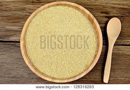 Amaranth seeds in a bamboo bowl on wooden table