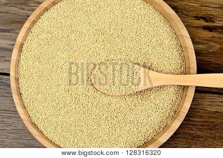 Healthy amaranth seeds in a bamboo bowl on wooden table