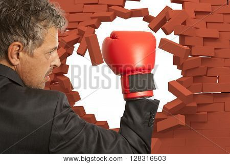 Businessman in red boxing gloves and brick wall