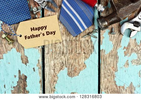 Happy Father's Day Tag And Top Border Of Tools On Rustic Blue Wood Background