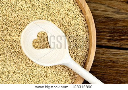Amaranth seeds in a bamboo and wooden spoon with heart shape on table