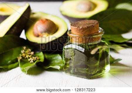 Avocado with leaves and jar of oil on white background. Closeup