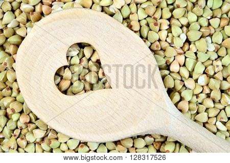 Wooden spoon with heart shape in a green buckwheat background