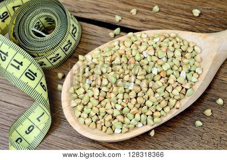 Green buckwheat in a wooden spoon and centimeter on table