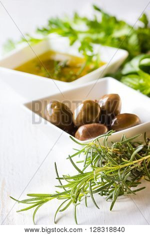 Olive oil olives and fresh herbs on white background. Greek mediterranean cusine concept.