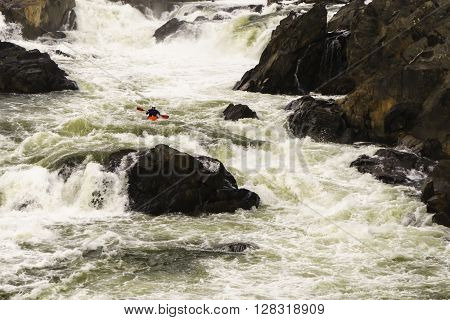 POTOMAC, MARYLAND, USA - NOVEMBER 28, 2015: A man navigates the turbulent whitewater of the Great Falls of the Potomac River.