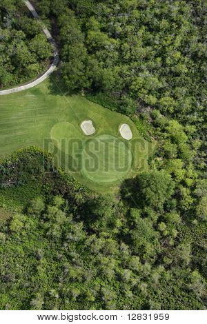Aerial view of golf hole on golf course surrounded by trees in Maui, Hawaii.